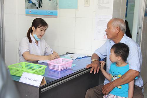 Gia đình đưa trẻ đến tiêm trong Chiến dịch tiêm bổ sung vắc xin sởi – rubella tại trạm Y tế phường An Hòa